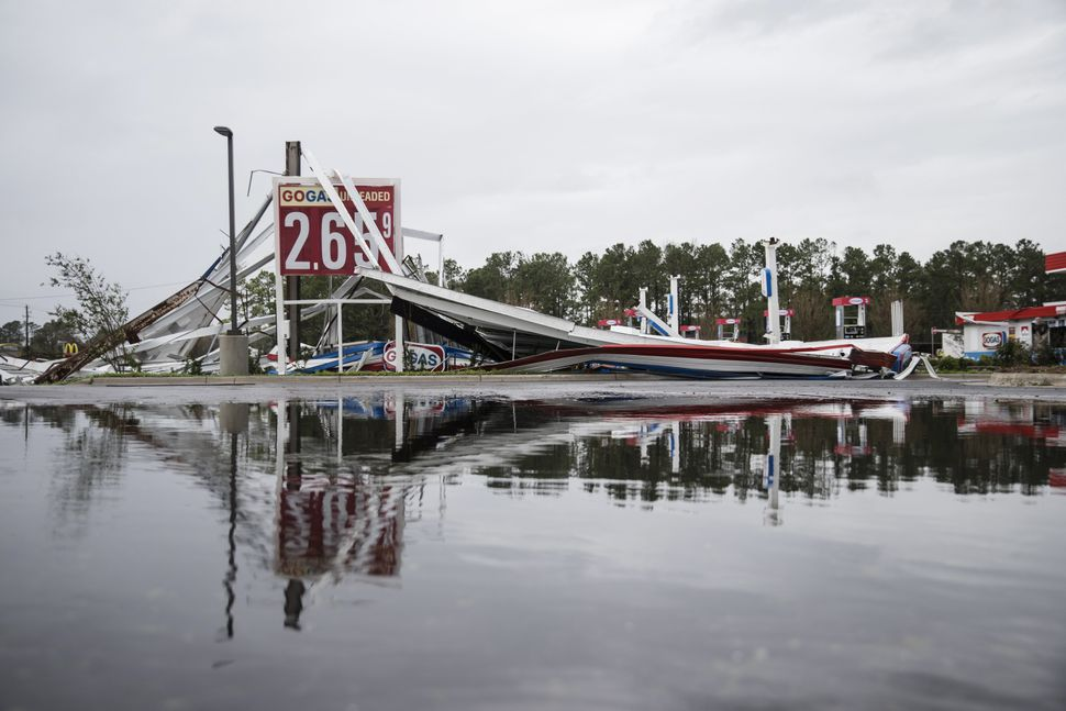 A damaged gas station is reflected in a puddle in Wilmington, North Carolina.