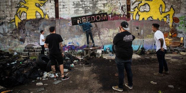 DETROIT, MI - SEPTEMBER 04:  Members of the band 'Freedom' spray paint their name on a wall at the abandoned Packard Automotive Plant on September 4, 2013 in Detroit, Michigan. The Packard Plant was a 3.5 million square foot car manufacturing plant built completed in 1911. Major operations ceased in 1958, though the plant was used in a limited capacity until the 1990s, with outer buildings used through the mid 2000s. Since then the buildings have fallen into disrepair - they are now used mostly for graffitti artists and scavengers. Detroit has an astonishing 78,000 abandoned buildings across its 142 square miles. Last month the city declared bankruptcy, the largest municipality to ever do so in the United States.  (Photo by Andrew Burton/Getty Images)