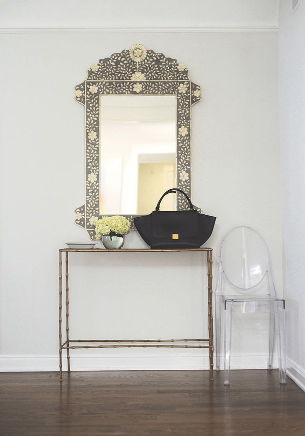 When it comes to decorating your entryway, less is more, Schuman writes. All you really need is a place to hang your keys, li