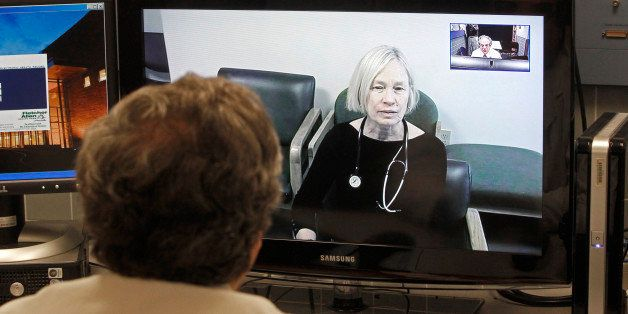 In this Thursday, Dec. 20, 2012 photo, Dr. Terry Rabinowitz, back to camera, talks with nurse Leslie Orelup at Helen Porter Nursing Home on in Burlington, Vt. New health insurance regulations in Vermont are giving a boost to telemedicine, the system that enables health care providers to offer consult with patients without being in the same room. Telemedicine isnᅢ까タᅡルt new, but the new regulations make it easier for physicians to be reimbursed for services performed by two-way video hookups. Fletcher Allen Telemedicine director Dr. Terry Rabinowitz says popular specialties are psychiatry and dermatology. (AP Photo/Toby Talbot)
