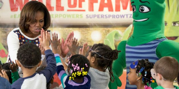 First lady Michelle Obama high-fives children after exercising and dancing with the Super Sprowtz during a visit to La Petite