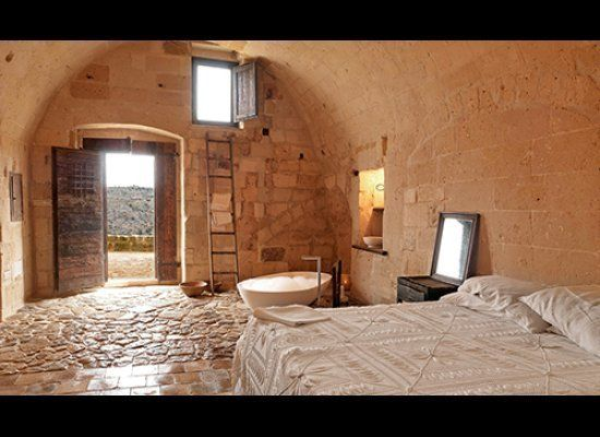 Fulfill medieval dungeon fantasies at the Sextantio Le Grotte Della Civita hotel in the Southern Italian village of Matera. Y