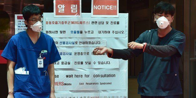 South Korean hospital workers wearing masks stand in front of a public notice on MERS while setting up a separated emergency center at the National Medical Center in Seoul on June 1, 2015. South Korean President Park Geun-Hye scolded health officials on June 1, over their response to an outbreak of the MERS virus, as the number of infections climbed to 18, with nearly 700 under observation. Major South Korean hospitals are setting up special MERS clinic rooms to fight the disease. AFP PHOTO / JUNG YEON-JE        (Photo credit should read JUNG YEON-JE/AFP/Getty Images)