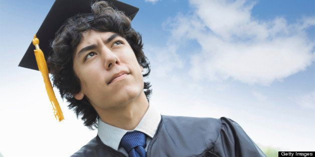 Contemplative young Asian man wearing graduation cap and gown