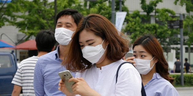 A woman wears a mask as a precaution against Middle East Respiratory Syndrome (MERS) virus as she uses her smartphone on a street in Seoul, South Korea, Tuesday, June 2, 2015. South Korea on Tuesday confirmed the country's first two deaths from MERS as it fights to contain the spread of the virus that has killed hundreds of people in the Middle East. (AP Photo/Ahn Young-joon)