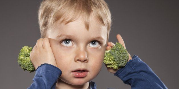 Portrait of little boy holding broccoli on his ears