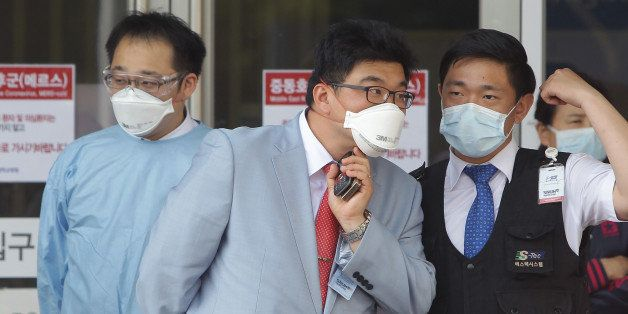 SEOUL, SOUTH KOREA - JUNE 02:  Hospital workers wearing masks to protect them against the MERS virus at a quarantine tent for people who could be infected with the MERS virus at Seoul National University Hospital on June 2, 2015 in Seoul, South Korea. The Ministry of Health and Welfare of South Korea confirmed two deaths from Middle East Respiratory Syndrome (MERS) on June 2, 2015. It reported six new cases of MERS, raising the number of confirmed local patients to 25. The first case was confirmed on May 20.  (Photo by Chung Sung-Jun/Getty Images)