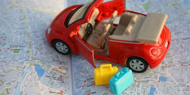 toy car on luggage on map of...