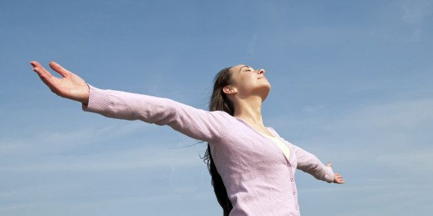 happy and healthy young woman with open arms against blue sky feeling freedom