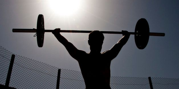 A participant in the 2011 Afghan Games power snatches a weighted bar on Sept. 10, 2011 at Kandahar Airfield, Afghanistan. During the second workout of the day, participants had to perform 50 burpees and as many power snatches as they could in a 10-minute period. Afghan Games is an annual Kandahar CrossFit event held to test the physical fitness levels of participants. (U.S. Air Force photo by Senior Airman David Carbajal)