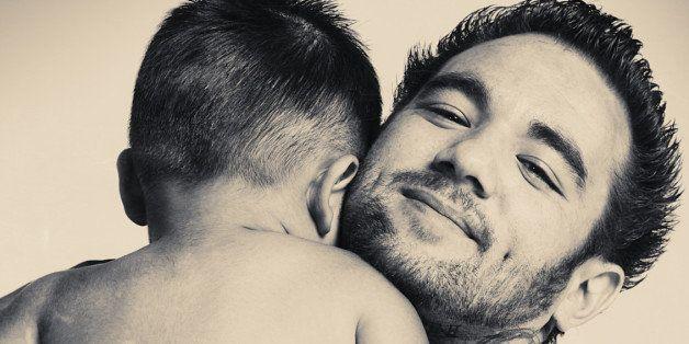 Baby boy and his dad hugging.