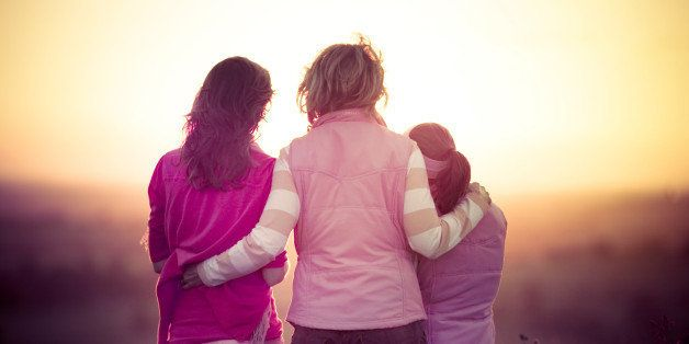 Rear view of mother and sisters watching sunset.