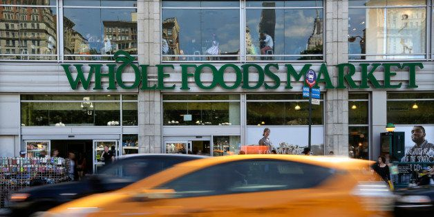 Pedestrians and motorists pass in front of a Whole Foods Market store in Union Square, Wednesday, June 24, 2015, in New York. New York City's consumer chief said Wednesday that Whole Foods supermarkets have been routinely overcharging customers by overstating the weight of prepackaged meat, dairy and baked goods. (AP Photo/Julie Jacobson)