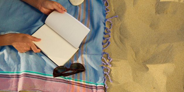 Woman on the beach reading a book