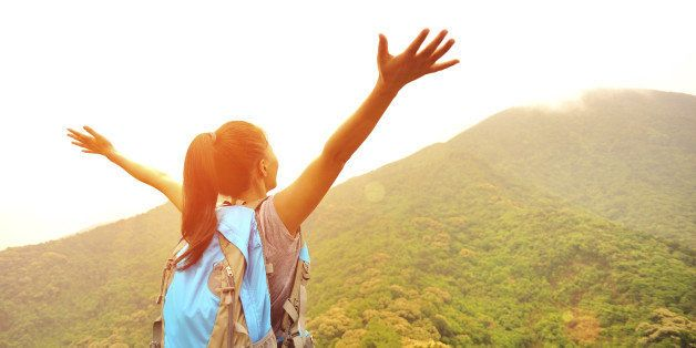 cheering hiking woman open arms at mountain peak