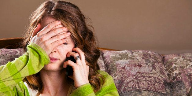 Attractive young woman receives bad news via mobile phone.