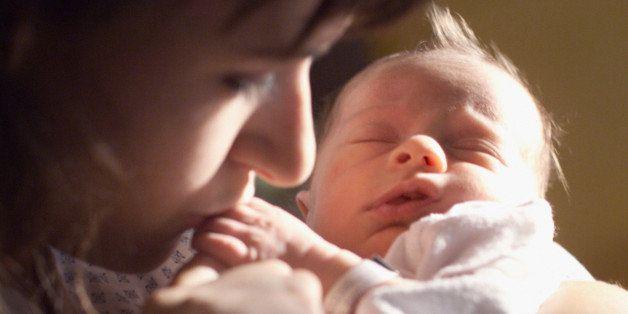 a caucasian brunette female mother holds her newborn baby