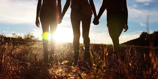 Silhouette of three girls walking into sunset