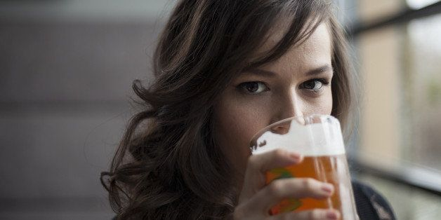 Portrait of a young woman drinking a pint glass of beer.