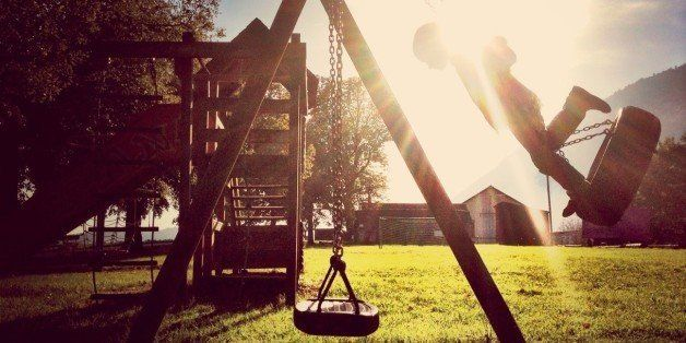 Boy On Tire Swing In Playground