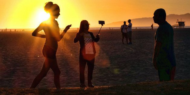 In this Friday, March 27, 2015 photo, a beachgoer using a cell phone on a stick snaps a selfie as the sun sets at Venice beach in Los Angeles. You can bring your beach towels and floral headbands, but forget that selfie stick if youᅢ까タᅡルre going to the Coachella or Lollapalooza music festivals. The sticks are banned this year at the events in Indio, California, and Chicago. Coachella dismissed them as ᅢ까タᅡワnarsissticsᅢ까タᅡン on a list of prohibited items. (AP Photo/Richard Vogel)