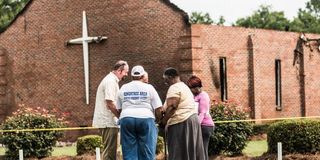 GREELEYVILLE, SC - JULY 1:  People pray near the burned ruins of the Mt. Zion AME Church July 1, 2015 in Greeleyville, South Carolina.  Federal and state agencies are investigating a recent string of church fires in the South that have occured since the church massacre in nearby Charleston, South Carolina. Mt. Zion AME was burned twenty years ago by members of the Ku Klux Klan. (Photo by Sean Rayford/Getty Images)