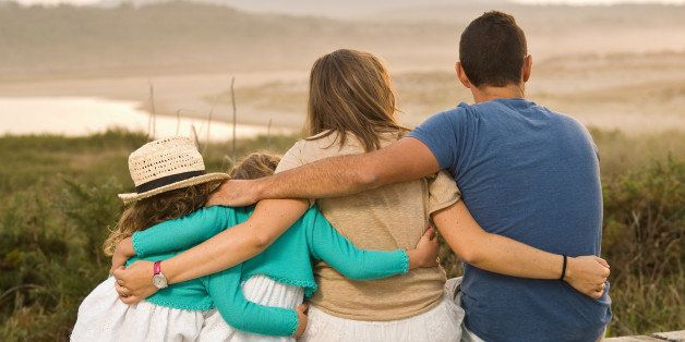 Family together and embracing on the beach