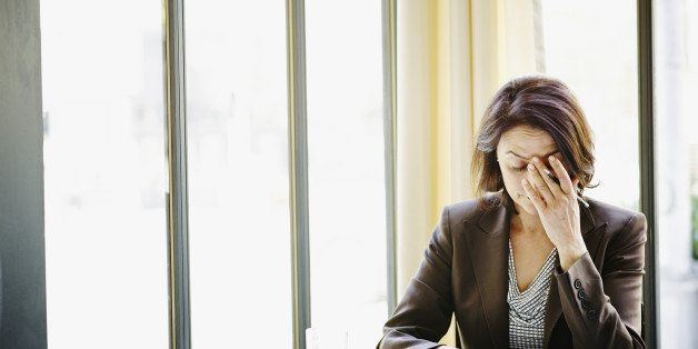 Businesswoman sitting at table in restaurant with head resting on hand