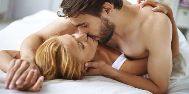 Hands of female and male lying on bed and kissing