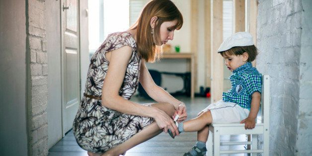 Mother putting shoes and socks on baby son