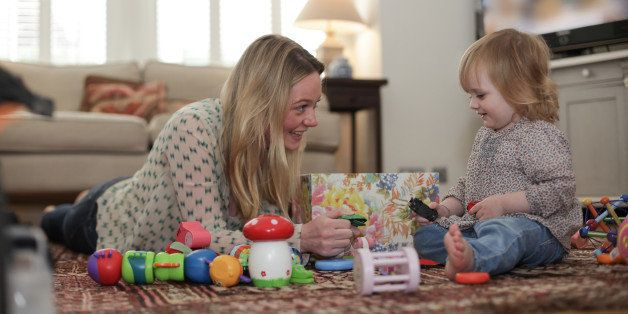 Mother and daughter playing with toys on living room floor