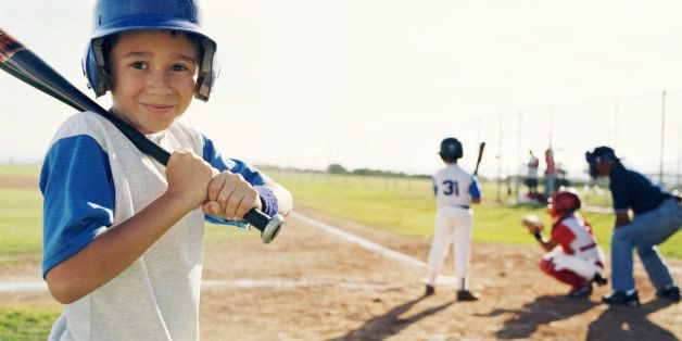 Little league player standing on side getting ready to play