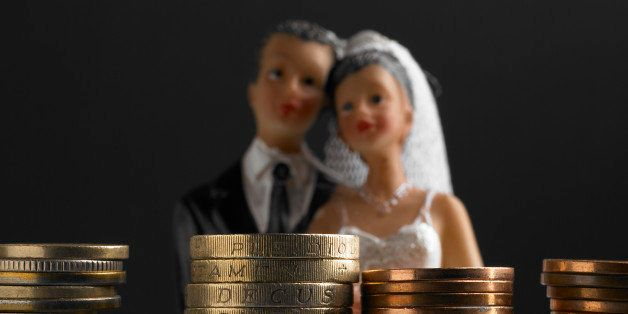 Bride and groom wedding figure standing in front of a stack of pound coins (Concept of the cost of weddings/pre nutual agreement)