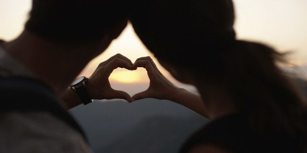 Cropped view of the silhouette of two hands making a heart-shape