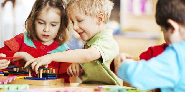 Cute cheerful children playing with toys. The focus is on the blonde boy.