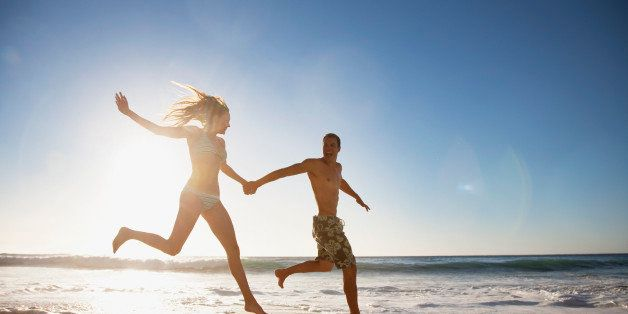 Couple holding hands and running on beach