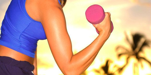 A close-up of a Caucasian female's arm curling a dumbbell