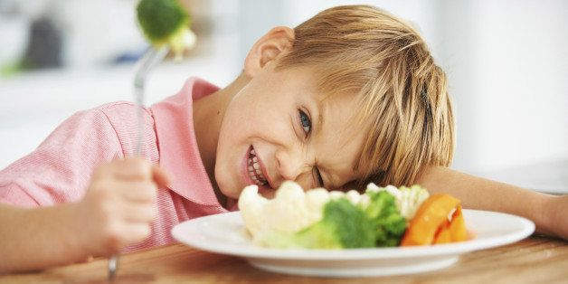 Portrait of a cute young boy looking naughty while holding a piece of broccoli on his fork