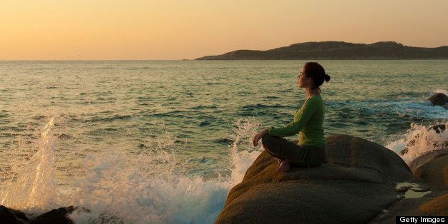 Woman practicing yoga near the sea at sunrise