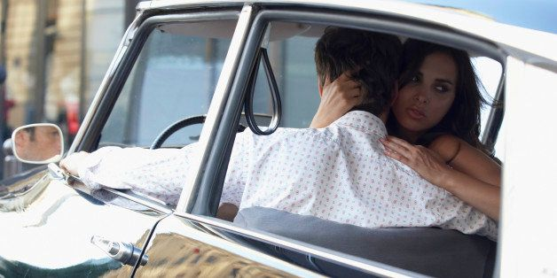 Couple in car, woman embracing man and looking over shoulder