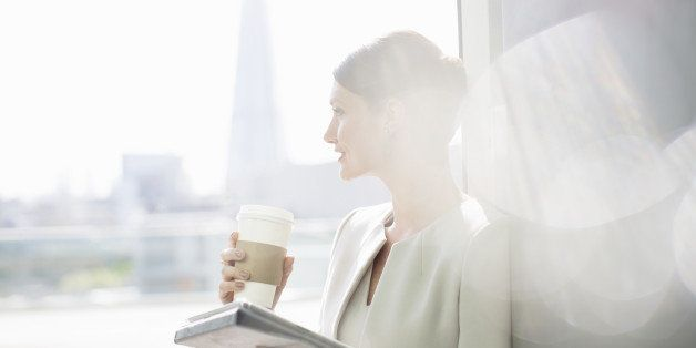 Businesswoman enjoying cup of coffee at window