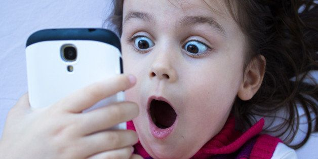 Portrait of a shocked little girl looking at phone. Horizontal composition. Image developed from Raw format. Little girl looking at phone and gesturing shock.