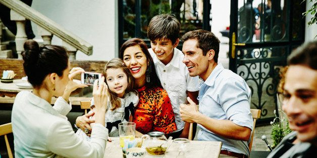 Smiling family posing for photo at table during family dinner party in restaurant