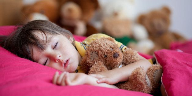 Sweet little boy, sleeping in the afternoon with his teddy bear toy