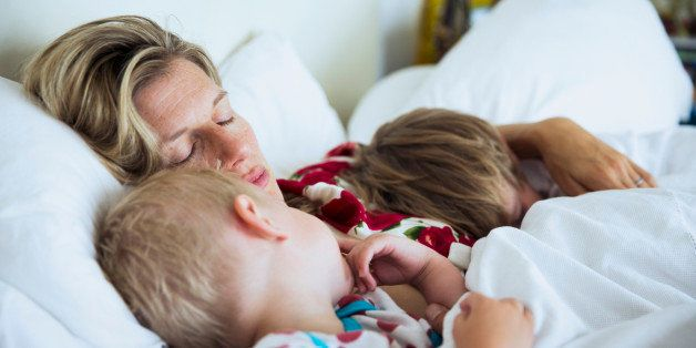 Mother with sons sleeping in bed