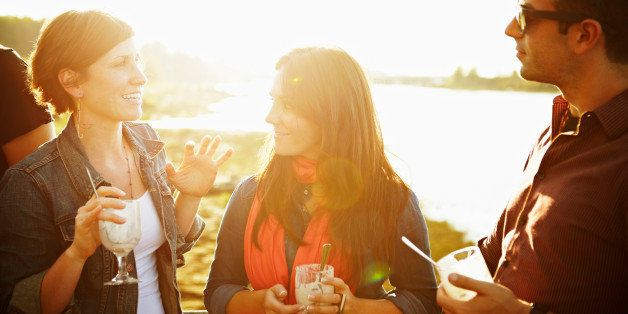 Group of three friends standing on dock at sunset eating dessert and talking