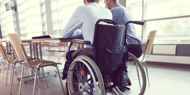 Disabled businessman sitting in a wheelchair at the conference table in board room and working with his colleague together. Back view, unrecognizable people.
