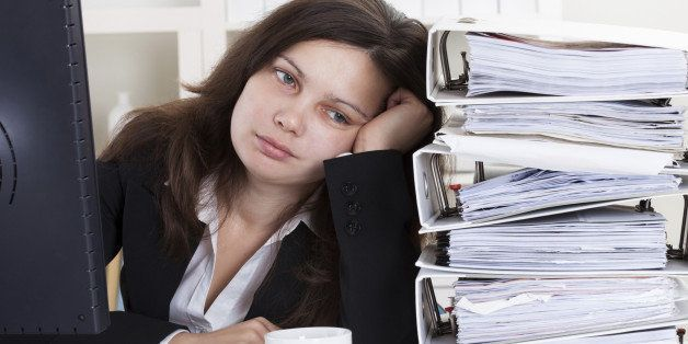 Stressed Businesswoman Working In Office With Stack Of Folders