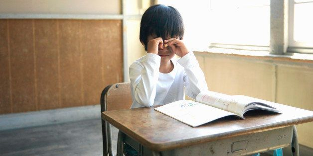 Boy (5-7) crying in school classroom