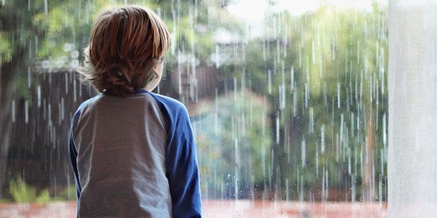 Young boy looking out window on a rainy rainy day, his reflection shown in the window glass.